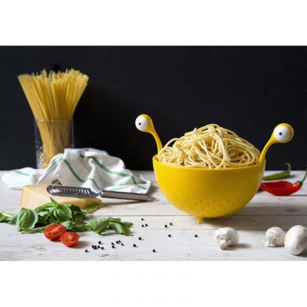 colador spaghetti monster en mesa de cocina con la pasta, albahaca, championes, queso, tomate...